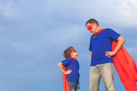 Father and son playing superhero at the day time