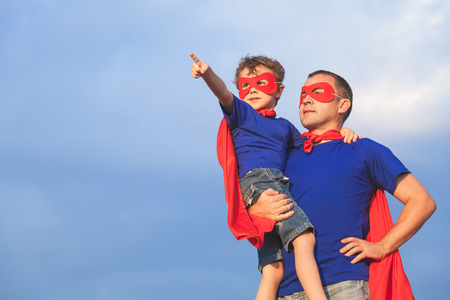 Ojciec i syn gra superbohatera w czasie dnia. Ludzie zabawy na wolnym powietrzu. Koncepcja przyjazny rodzinie.