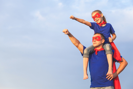 Father and daughter playing superhero at the day time
