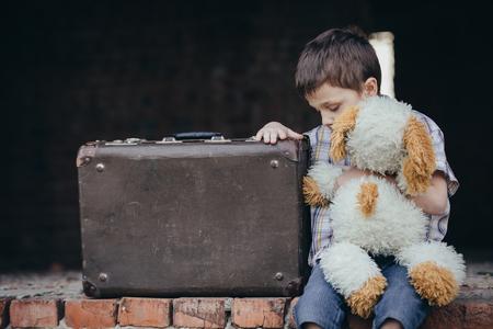 日にスーツケースを持って座っている屋外悲しい小さな少年の肖像画。悲しみのコンセプトです。 写真素材