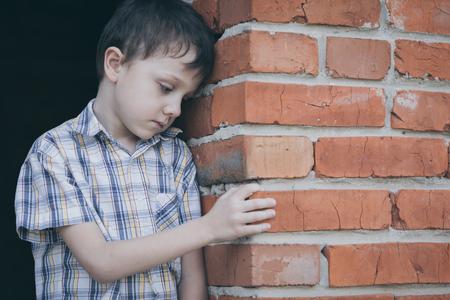 Portret van trieste jongetje buiten op de dag de tijd. Concept van verdriet.