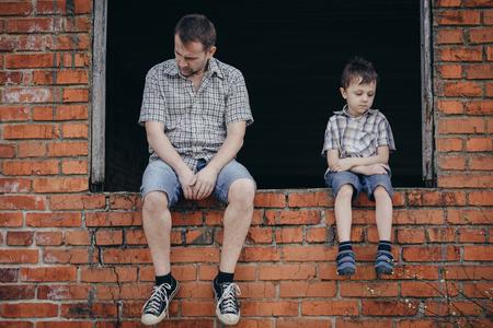 Portrait de jeune triste petit garçon et son père assis à l'extérieur au moment de la journée. Concept de la douleur. Banque d'images - 75829754