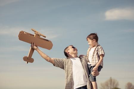 Père et fils jouant avec un avion jouet en carton dans le parc à la journée. Concept de famille amicale.