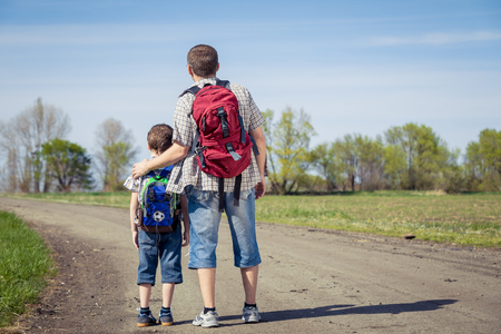 Father and son walking on the road at the day time. People having fun outdoors. Concept of friendly family. Stock Photo - 76872230