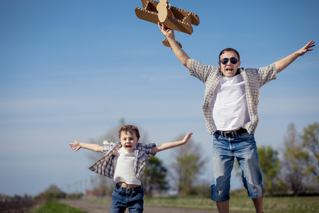Father and son playing with cardboard toy airplane in the park at the day time. Concept of friendly family. Stock Photo