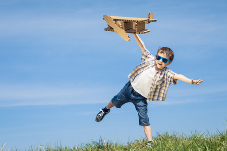 Little boy playing with cardboard toy airplane in the park at the day time. Concept of happy game. Child having fun outdoors. Picture made on the background of blue sky. Stock Photo