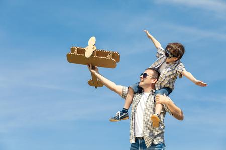 Padre e hijo jugando con avión de juguete de cartón en el parque a la hora del día. Concepto de familia amistosa. Gente que se divierte al aire libre. Imagen hecha en el fondo del cielo azul. Foto de archivo - 77786060