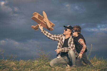 父と息子の日に公園で段ボールのおもちゃの飛行機で遊んで。フレンドリーな家族の概念。人々 は屋外の楽しい時を過します。濃い青空を背景に作 写真素材