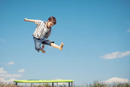 he: Little boy playing on the field at the day time. People having fun outdoors. He jumping on trampoline on the lawn. Concept of friendly family. Stock Photo