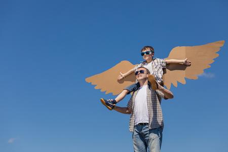 아버지와 아들 하루 시간에 공원에서 골 판지 장난감 날개를 가지고 노는. 친절 한 가족의 개념입니다. 사람들은 야외에서 재미입니다. 푸른 하늘 배경 스톡 콘텐츠