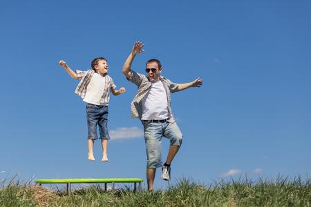 Vader en zoon spelen op het veld op de dag tijd. Mensen hebben plezier buitenshuis. Zij springen op trampoline op het gazon. Concept van vriendelijke familie. Stockfoto