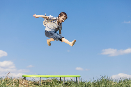 Little boy playing on the field at the day time. People having fun outdoors. He jumping on trampoline on the lawn. Concept of friendly family. Standard-Bild