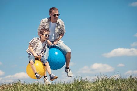 아버지와 아들 하루 시간에 필드를 재생합니다. 사람들은 야외에서 재미입니다. 그들은 잔디밭에 풍선 공을에 점프. 친절 한 가족의 개념입니다. 스톡 콘텐츠 - 78649106