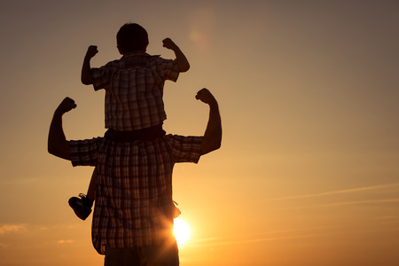 Father and son walking on the field at the sunset time. Concept of friendly family.