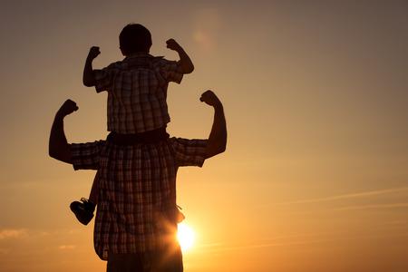 Vater und Sohn gehen auf dem Feld bei der Sonnenuntergangzeit. Konzept der freundlichen Familie.