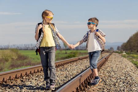 Gelukkige broer en zus lopen op de spoorweg op de dag tijd. Mensen hebben plezier buitenshuis. Concept van vriendelijke familie.