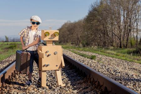 幸せの小さな少年とロボット日時鉄道のスーツケースを持って歩いています。彼は楽しいが屋外です。幸せなゲームのコンセプト。