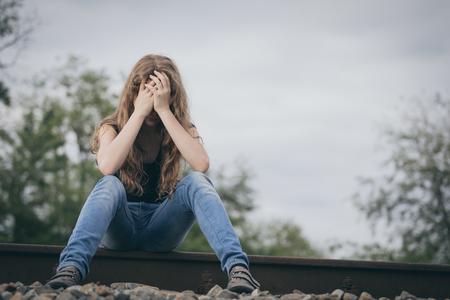 一日の時間で鉄道上屋外に座って悲しい 10 少女の肖像画。悲しみのコンセプトです。 写真素材