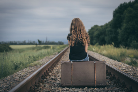 Portrait der jungen traurigen zehn Mädchen sitzen mit Koffer draußen auf der Eisenbahn am Tag Zeit. Konzept der Sorge. Standard-Bild