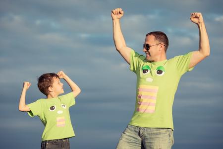 아버지와 아들은 낮 시간에 도로에 산책. 사람들은 야외 재미. 친화적 인 가족의 개념.