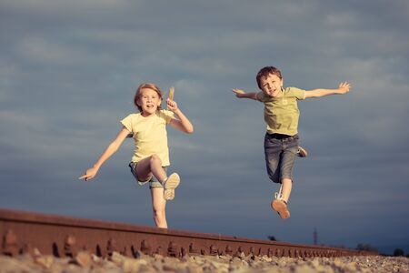 Brother and sister playing on the field at the day time. Children having fun outdoors. They running on the railway. Concept of friendly family. photo