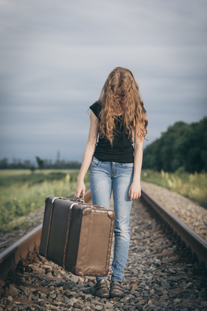 Portrait of young sad ten girl standing with suitcase outdoors  on the railway at the day time. Concept of sorrow. Stock Photo