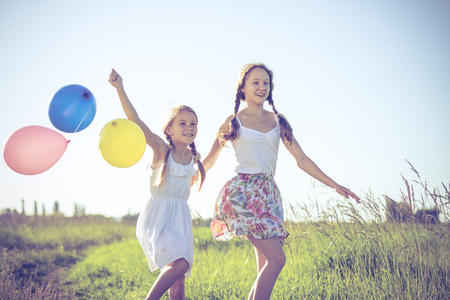 Happy little children playing in the field at the day time. They walking on the road  in the park and holding balloons  in the hands. Kids having fun on the nature. Concept of happiness. photo