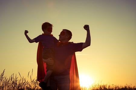 Padre e hijo que juegan al super héroe en la puesta del sol. Gente que se divierte al aire libre. Concepto de familia amistosa. Foto de archivo - 83688016