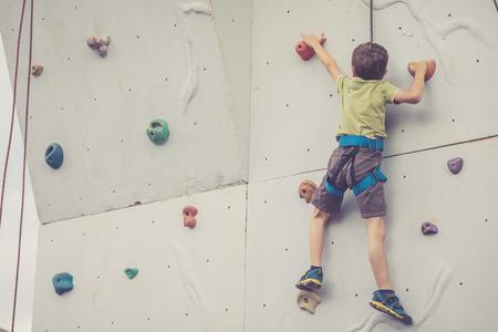 little boy climbing a rock wall outdoor. Concept of sport life.