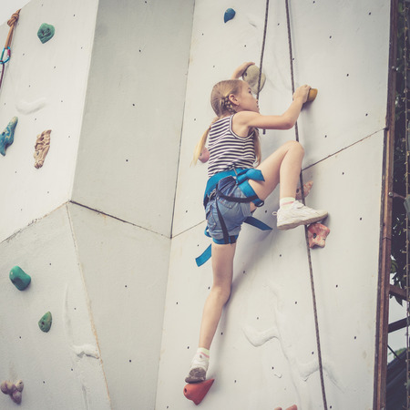 little girl climbing a rock wall outdoor. Concept of sport life.