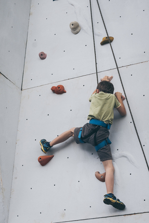 little boy climbing a rock wall outdoor. Concept of sport life.