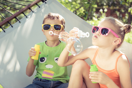 Two happy children lie on a hammock and play with soap bubbles. Concept carefree childhood Reklamní fotografie