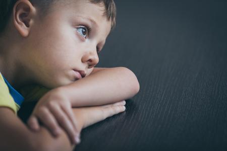 Portrait of one sad little boy. Concept of sorrow. Standard-Bild