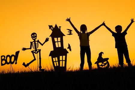 Gelukkige broer en zus spelen buiten in de zonsondergang tijd. Kinderen hebben plezier. Concept van happy Halloween-feest.