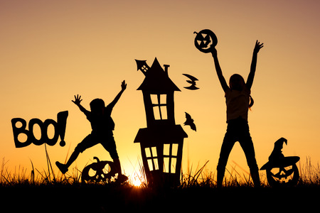 Happy brother and  sister playing outdoors at the sunset time. Kids having fun. Concept of happy Halloween party. Stock Photo