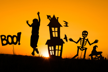 Happy little boy playing outdoors at the sunset time. Kid having fun. Concept of happy Halloween party. Stock Photo