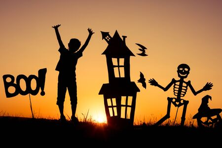 skeleton costume: Happy little boy playing outdoors at the sunset time. Kid having fun. Concept of happy Halloween party. Stock Photo