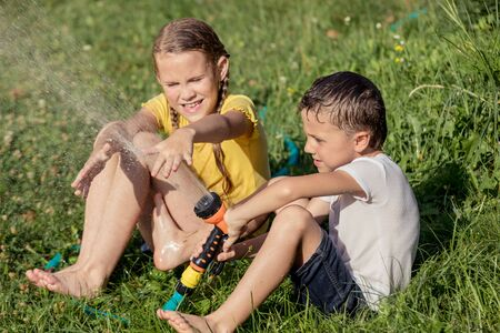 Happy kids sitting on the grass and pouring water from a hose. Concept Brother And Sister Together Forever Stock Photo