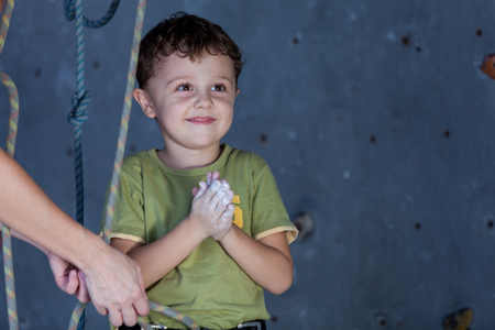 little boy and mother standing near a climbing  rock wall indoor.Concept of sport life.