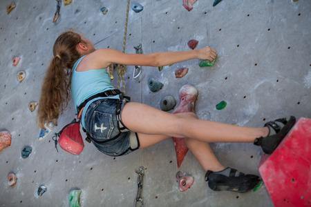 Teen girl climbing a rock wall indoor. Concept of sport life. Stock Photo
