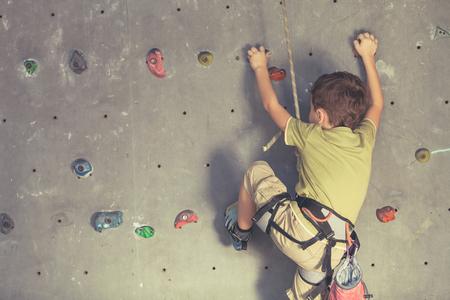 Ragazzino arrampicata su una parete di roccia coperta. Concetto di vita sportiva. Archivio Fotografico - 96197877
