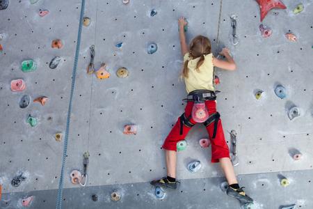 little girl climbing a rock wall indoor. Concept of sport life.