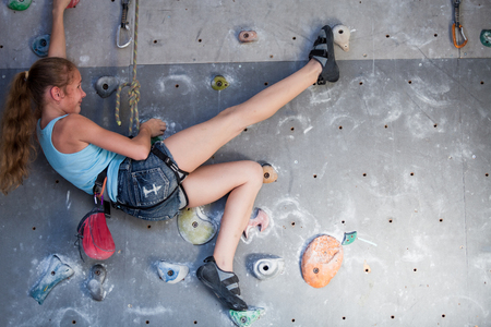 Teen girl climbing a rock wall indoor. Concept of sport life. Stock Photo