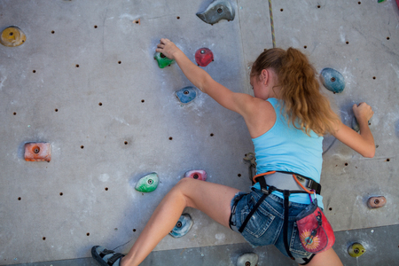 Teen girl climbing a rock wall indoor. Concept of sport life. Banco de Imagens