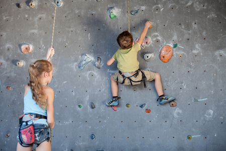 brother and sister standing near a rock wall for climbing indoor Concept of sport life.