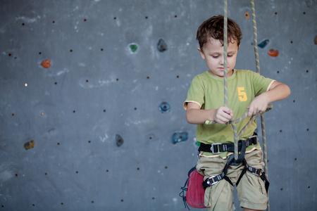 little boy standing near a climbing  rock wall indoor. Concept of sport life.