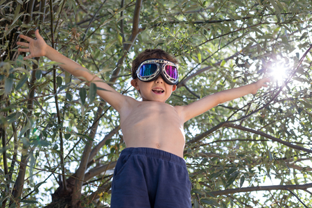 Happy little boy playing outdoors near a tree at the day time. Stock Photo