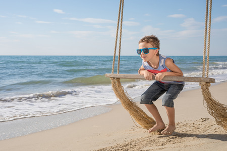 One happy little boy playing on the beach at the day time.  Kid having fun outdoors. Concept of summer vacation. 写真素材