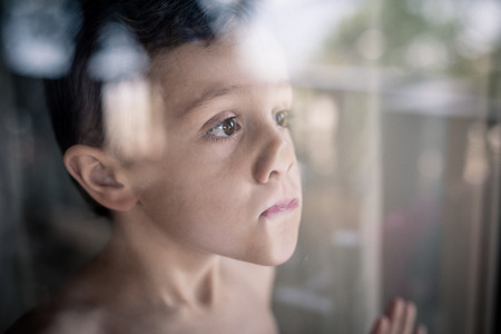 one sad little boy standing near the window at the day time. Concept of sorrow. Stock Photo