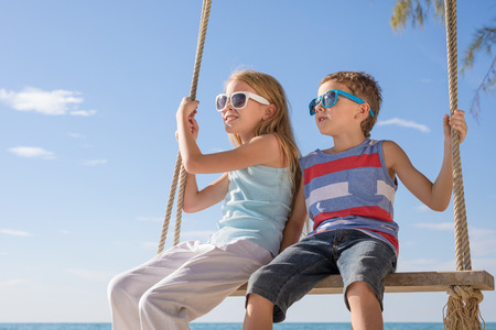 Two happy little children in the big sunglasses playing on the beach at the day time.  Kids having fun outdoors. Concept of summer vacation and friendly family.